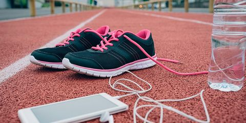 running shoes, an iPhone, and a water bottle on a track