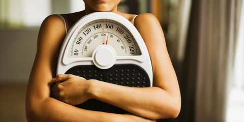 Woman clutching a weight scale