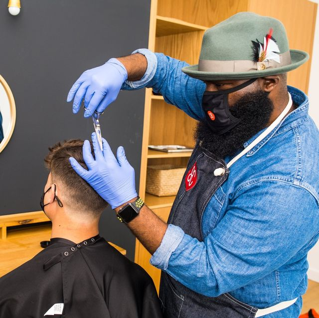 shortcut barber giving an in home haircut while wearing a mask during the coronavirus epidemic