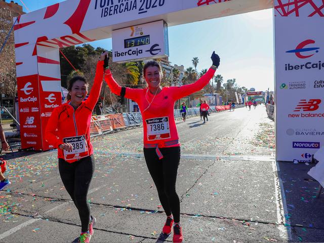 dos corredoras levantan los brazos triunfantes tras cruzar la meta del 10k valencia ibercaja