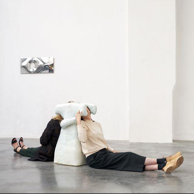 White, Shoulder, Joint, Human body, Floor, Performance art, Leg, Flooring, Photography, Sitting,