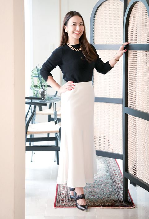白のサテンスカートを着る奥田麻弥子さん