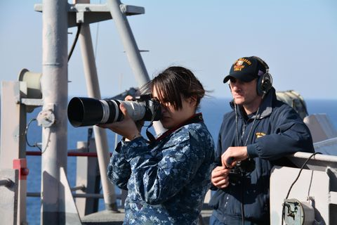 intelligence specialist 2nd class samantha fallon photographs a surface contact during a ship's nautical or otherwise photographic intelligence exploitation snoopie team evolution aboard the amphibious assault ship uss peleliu lha 5 peleliu is conducting sea trials in preparation for an upcoming deployment us navy photo by mass communication specialist 3rd class dustin knightreleased