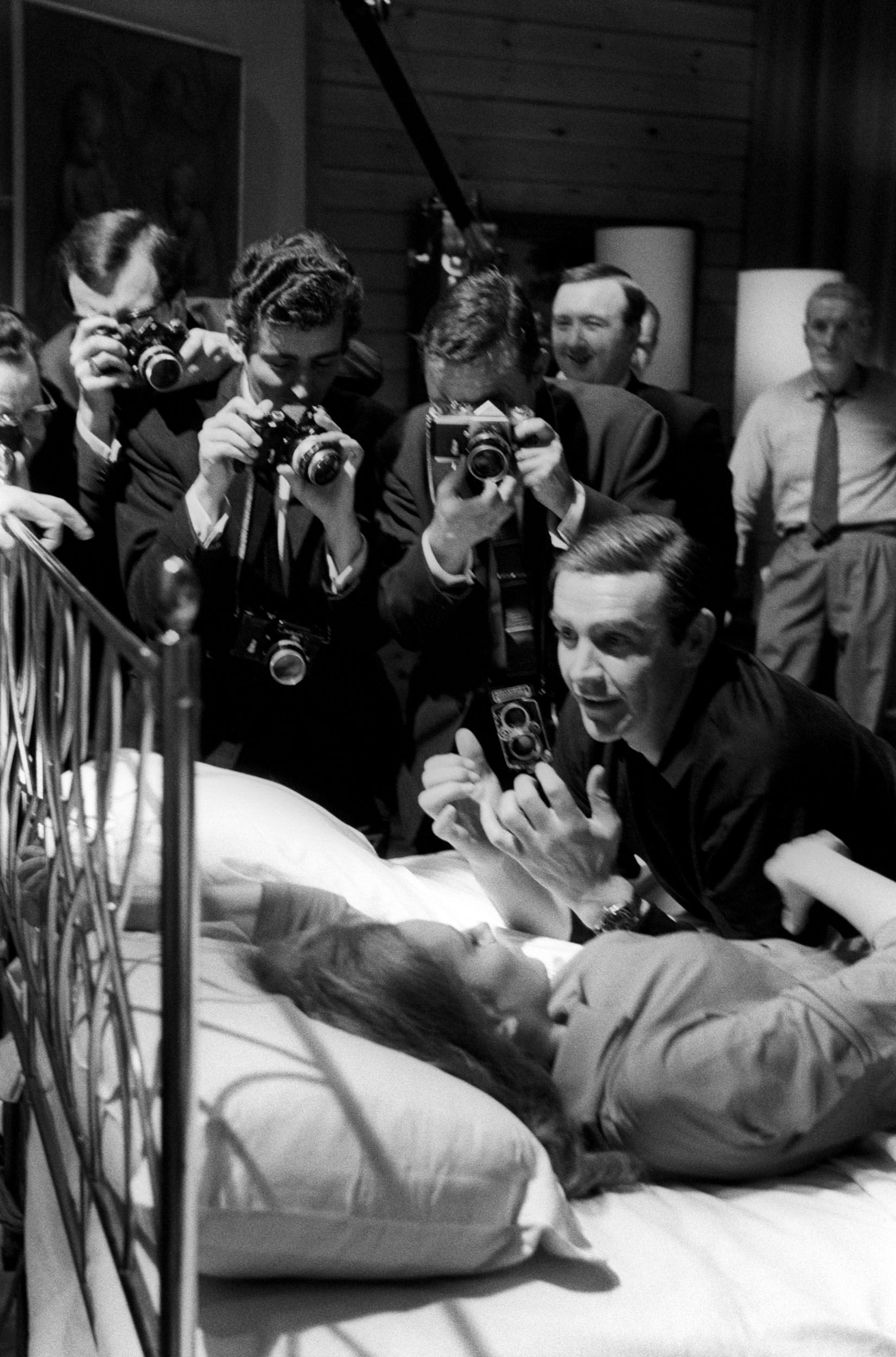 Sean Connery and Luciana Paluzzi are besieged by photographers during the shooting of a hot scene from Thunderball.
