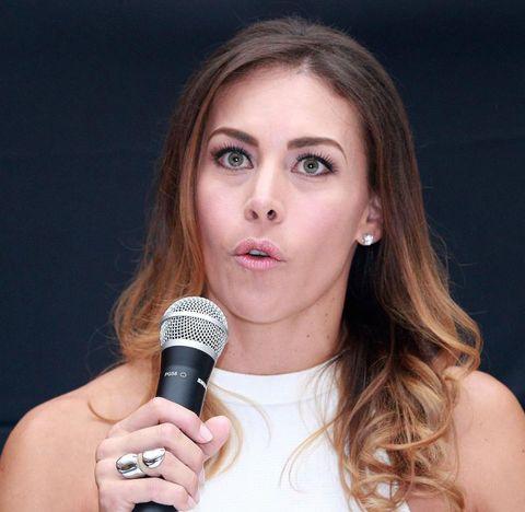 Vanessa Guzmán, con el pelo suelto y un micrófono, en rueda de prensa