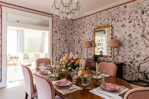 dining room, pink floral wallpaper, oval wooden table with pink velvet dining chairs, floral arraignment