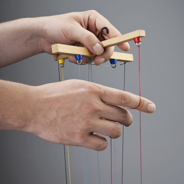 two hands operating a puppet
