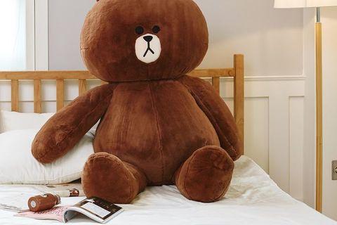 咖啡色的熊大坐在白色床上