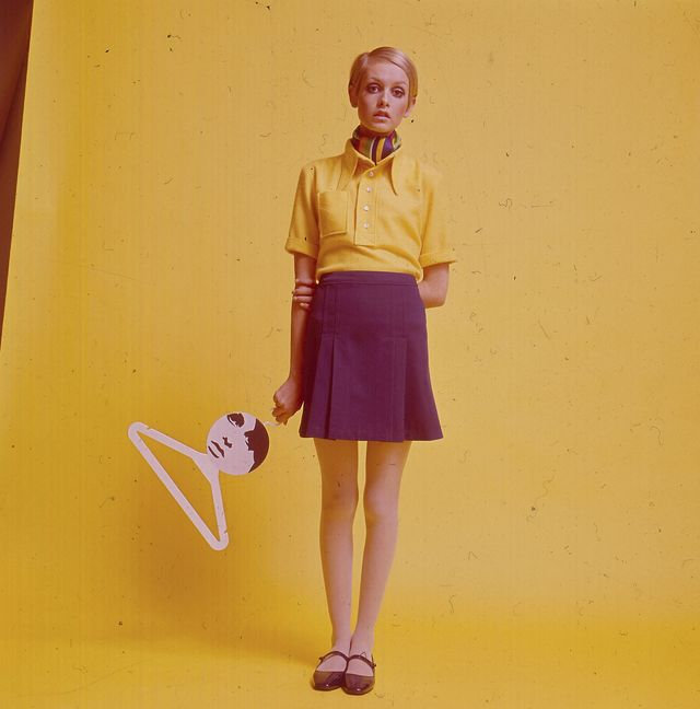 english fashion model twiggy stands wearing a yellow shirt, scarf and mini skirt and flat mary jane shoes whilst holding a coat hanger bearing her image in 1967 photo by popperfoto via getty imagesgetty images