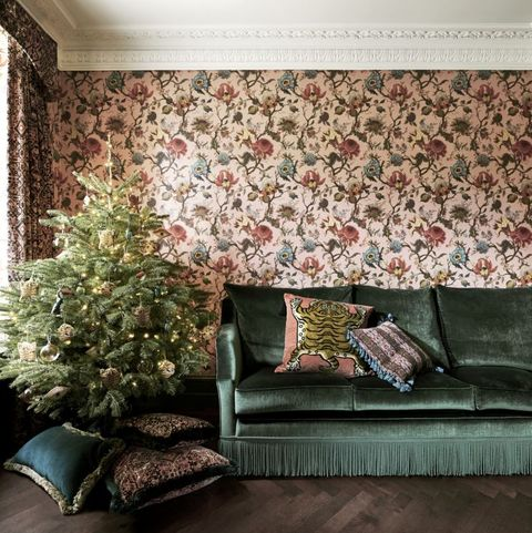 Living room with green velvet sofa and Christmas tree against floral patterned wallpaper