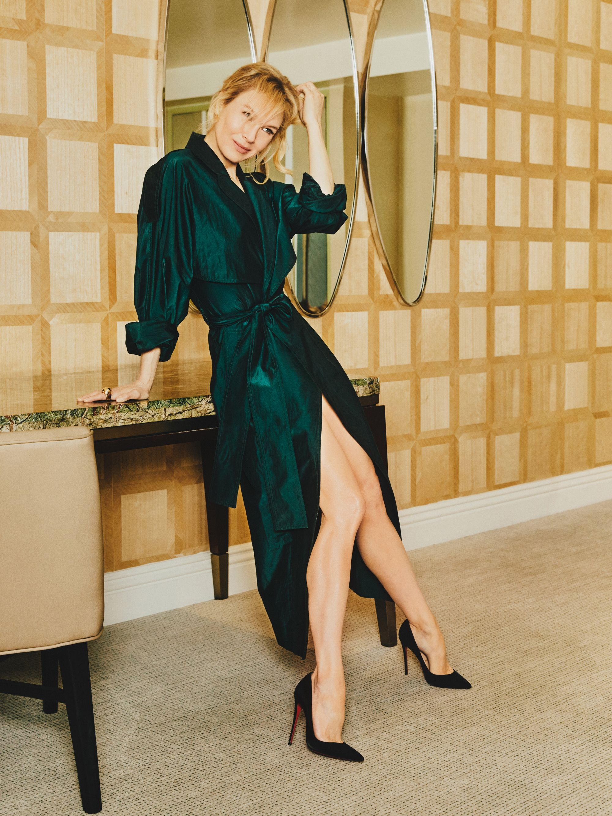 Zellweger wears a Victoria Beckham green trench dress, Cartier rings, and Christian Louboutin suede pumps.