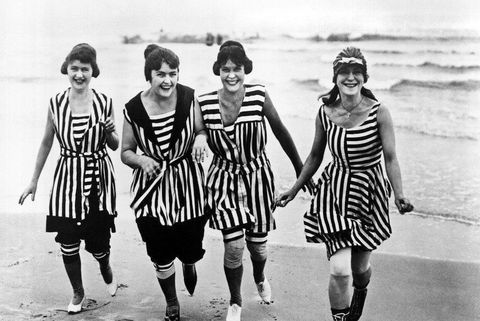 women dressed in bathing suits walk arm in arm on a sandy beach, 1910