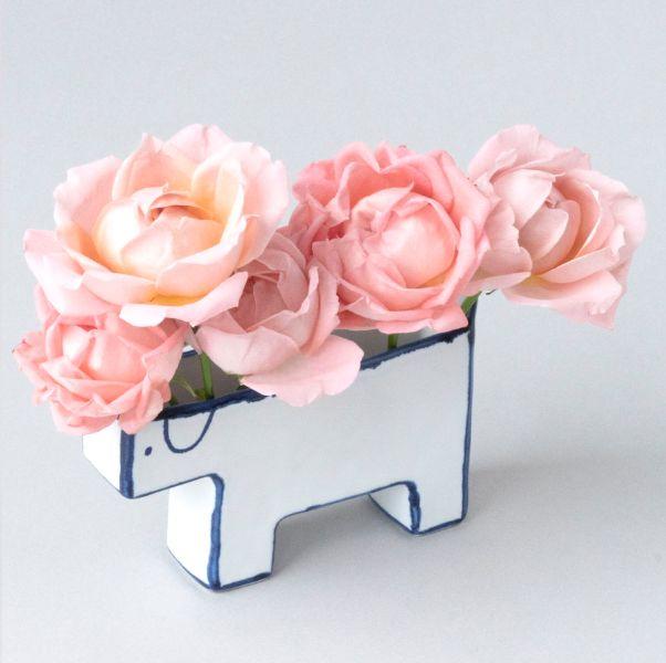 平面的狗狗花瓶上面有粉紅色的花