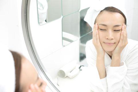 洗面所で鏡の前で肌をほほに当てている女性