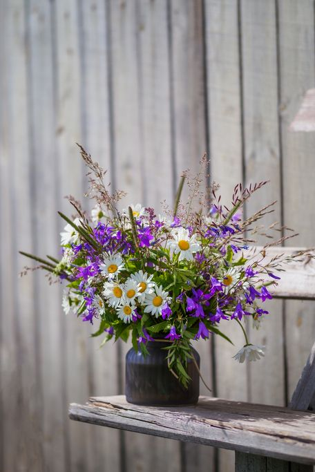 bouqet with wild flowers on old wooden bench field flowers bouqet with campanula and camomile cottagecore and farmcore concept copy space