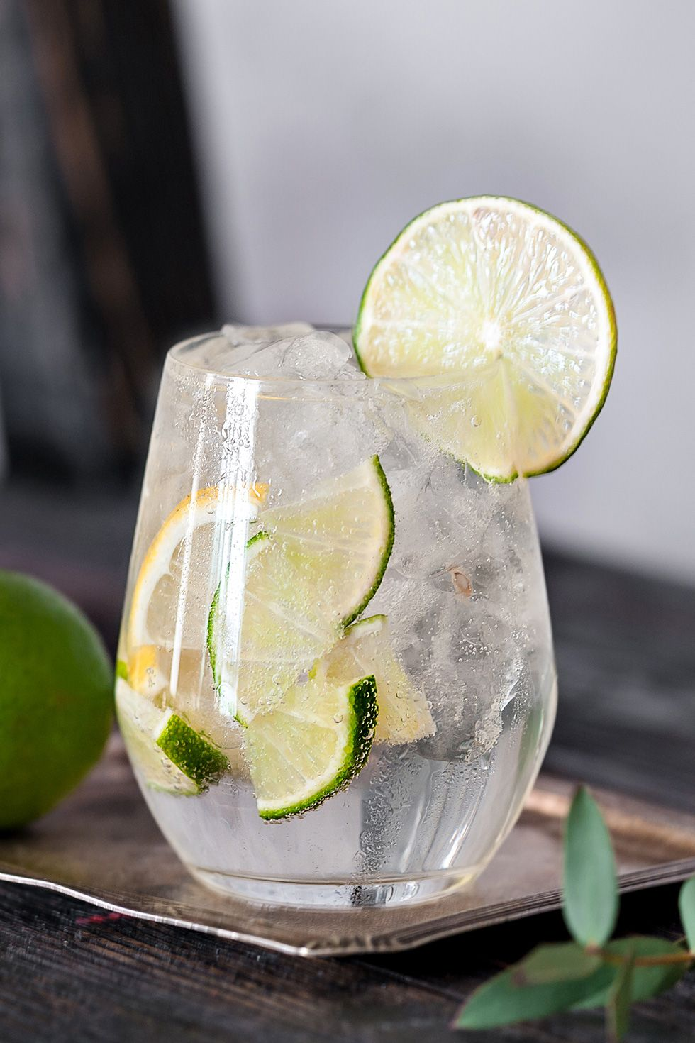 sparkling water in glass with cut lemons and limes