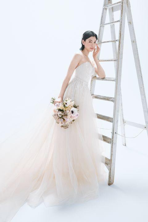 オフホワイトとピンクベージュのチュールドレスを着た三吉彩花さん