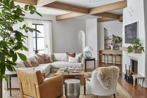 living room, white walls, wooden beams, white sofa, brown leather chair