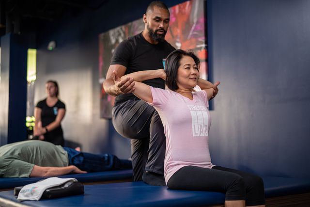 man helping a woman stretch in a class