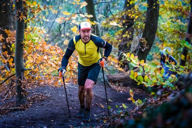 man in geel shirt op berg aan het trailrunnen in het bos