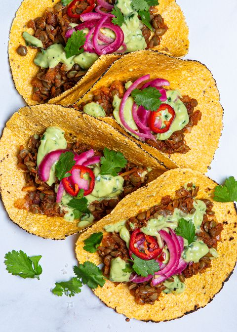 vegan tacos made with lentils in flour tortillas with pickled onions, green sauce, and cilantro
