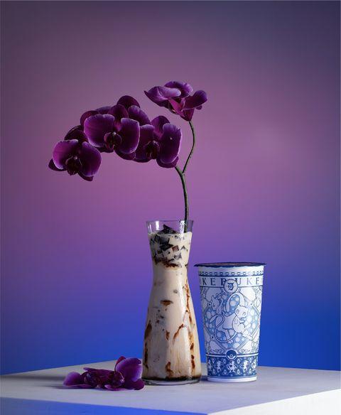 紫色的飲料旁邊有藍白色的杯子