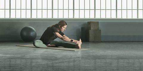 vrouw doet stretchoefeningen op een yogamatje met smartwatch om van garmin