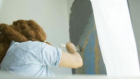 woman on ladder painting
