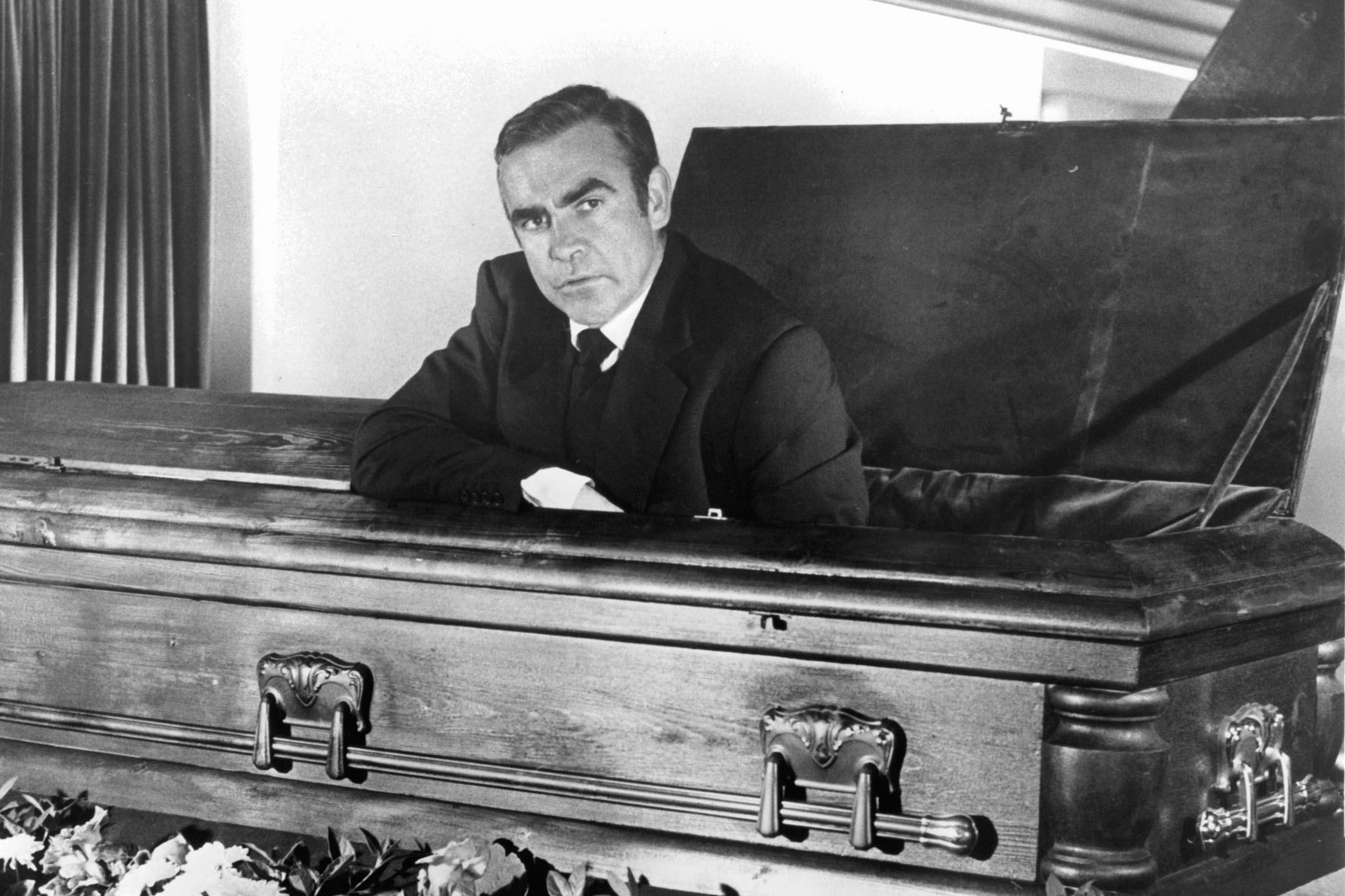 Sean Connery sitting in a coffin in a scene from Diamonds Are Forever.