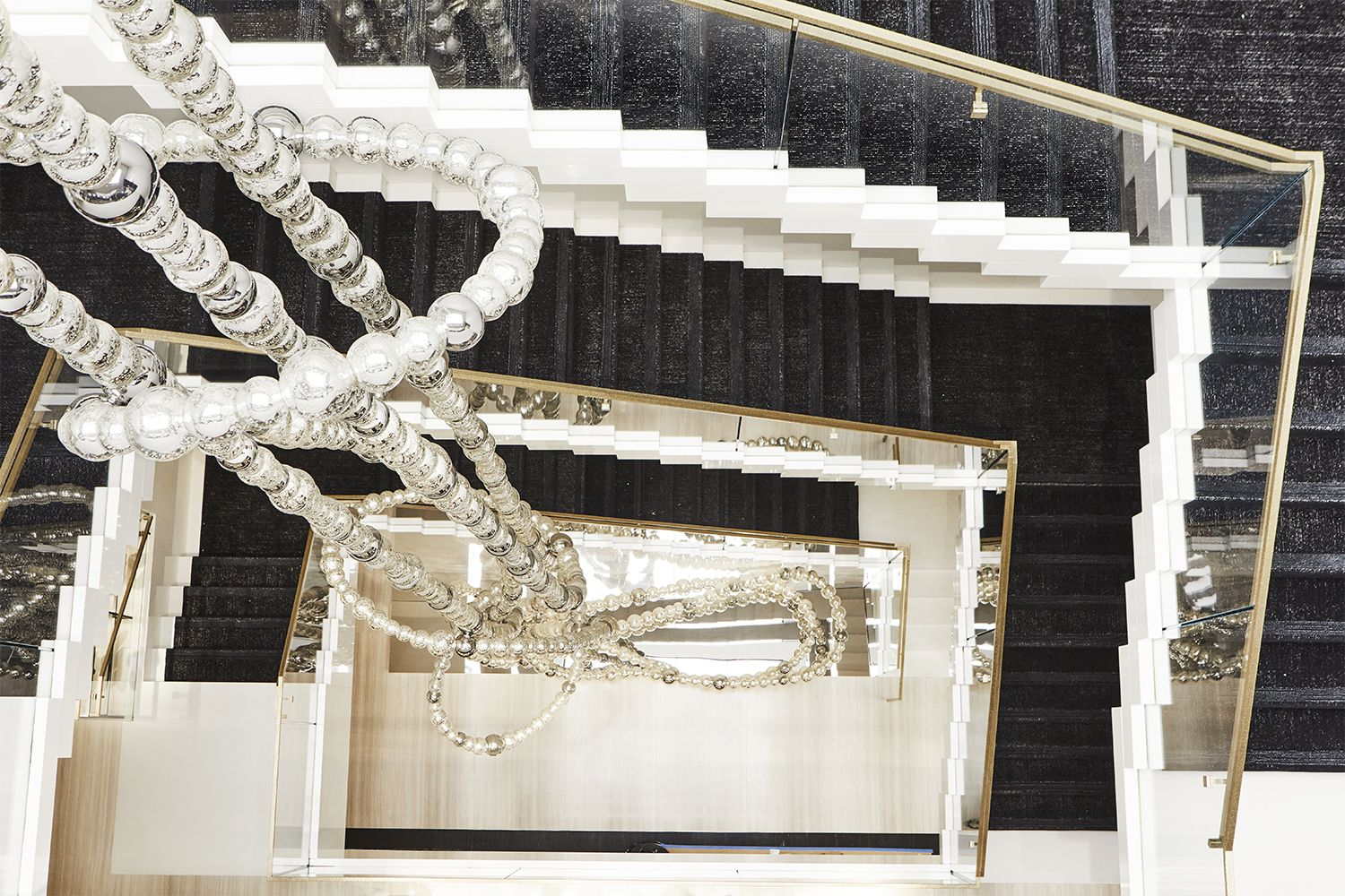 The sculpture, designed by Jean-Michel Othoniel, extends down a central staircase within the store.