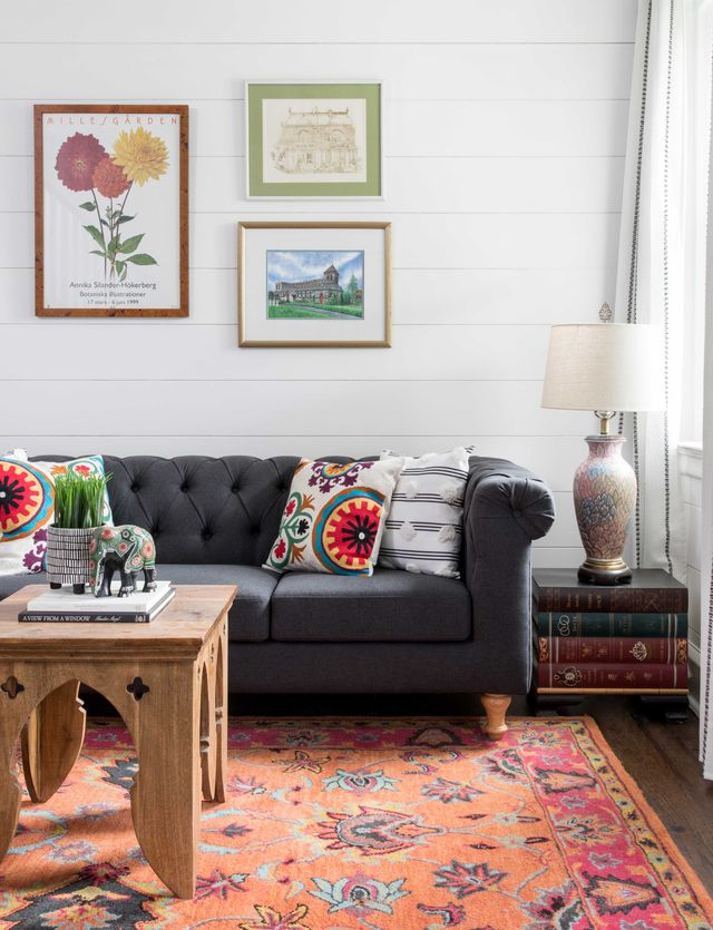 gray couch with colorful cushions, orange area rug, wooden coffee table, book side table