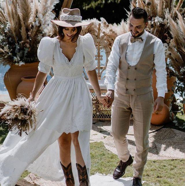 vestido de novia asimétrico y botas cowboy