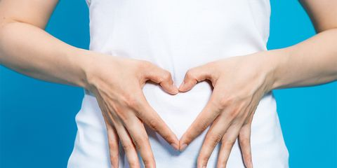 woman with hands on stomach heart shape