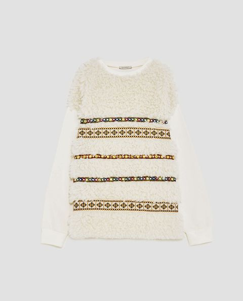 White, Clothing, Sleeve, Yellow, Beige, Outerwear, Sweater, Top, Font, Pattern,