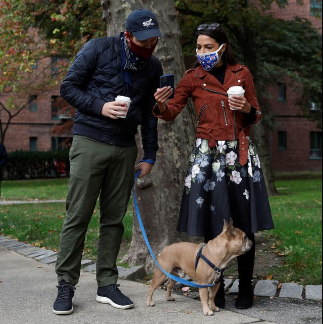 2d7w3f0 congresswoman alexandria ocasio cortez r stands in line with her partner riley roberts and her french bulldog named deco as she waits to vote early at a polling station in the bronx, new york city, us, october 25, 2020 reutersandrew kelly