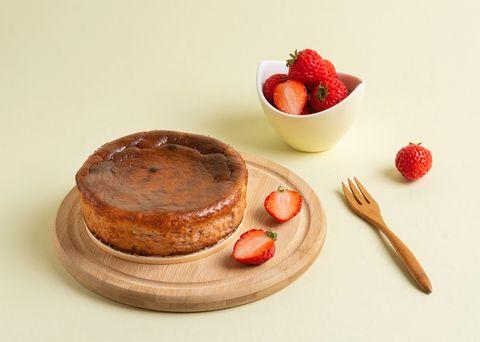 黃色背景前有咖啡色的「草莓巴斯克起司蛋糕」和紅色草莓