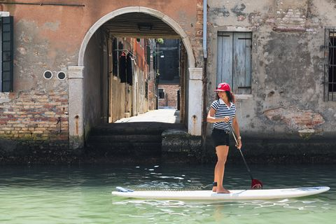 Stand up paddle surfing, Water, Waterway, Surface water sports, Canal, Standing, Paddle, Surfing Equipment, Recreation, Water sport,