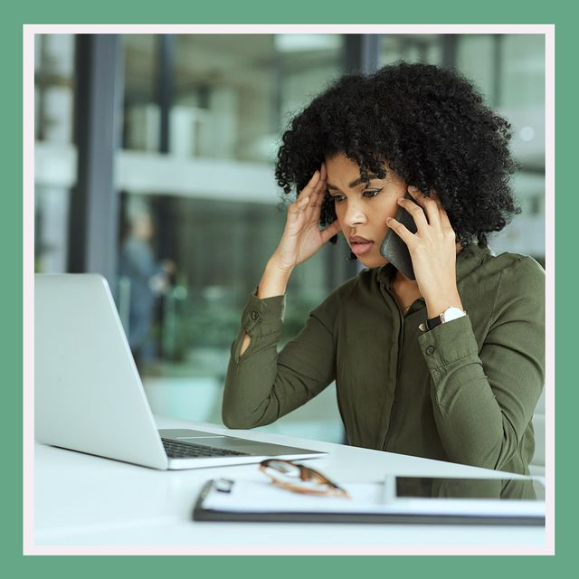 woman on computer and phone looking stressed