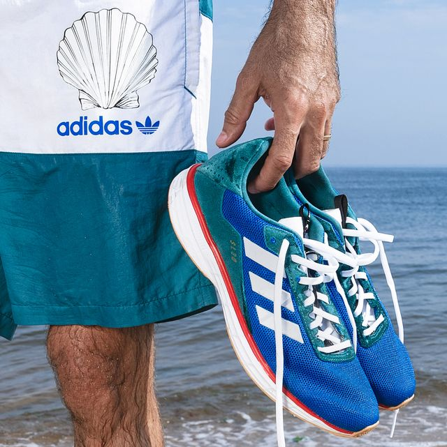 person holding sneakers in front of the ocean