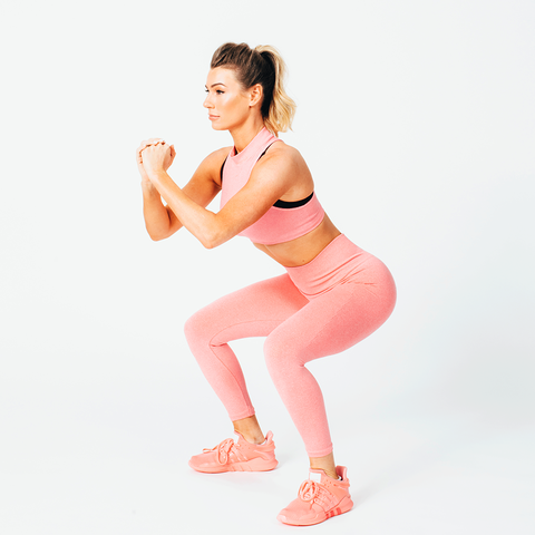 anna victoria performing a squat in a pink outfit