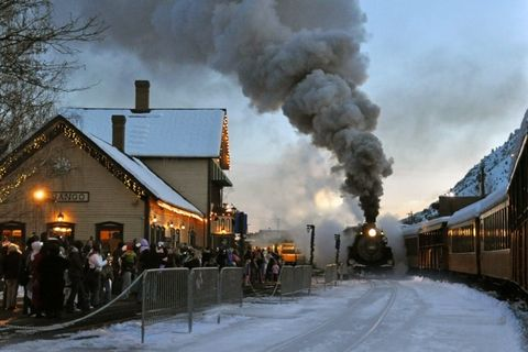 antique train with smoke billowing from it's stack pulling into an old fashioned depot with people lined up waiting to get on the train it is dusk out, and there is snow on the ground