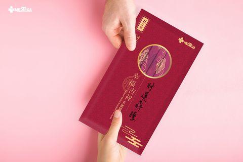 粉色背景有兩隻口拿著紅包包裝的口罩