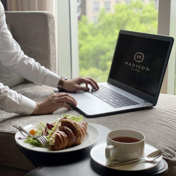 一個穿白襯衫的人正在用電腦前面也可頌跟咖啡