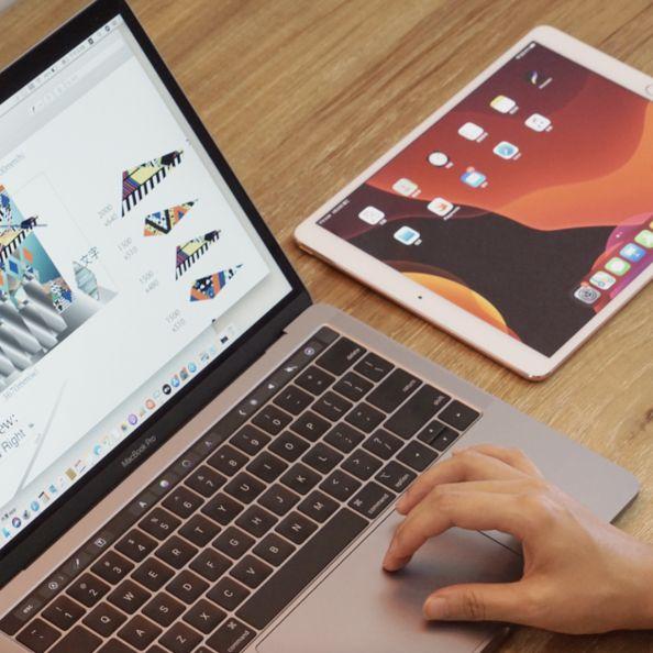 一個人在用電腦旁邊擺著咖啡色螢幕的ipad