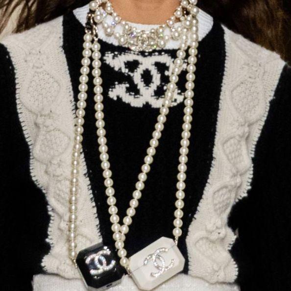 一個穿黑白色香奈兒上衣的女生戴著黑色和白色的airpods收納套