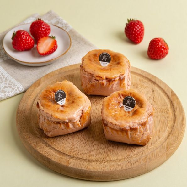 黃色背景前有紅色草莓和粉咖啡色的蛋糕