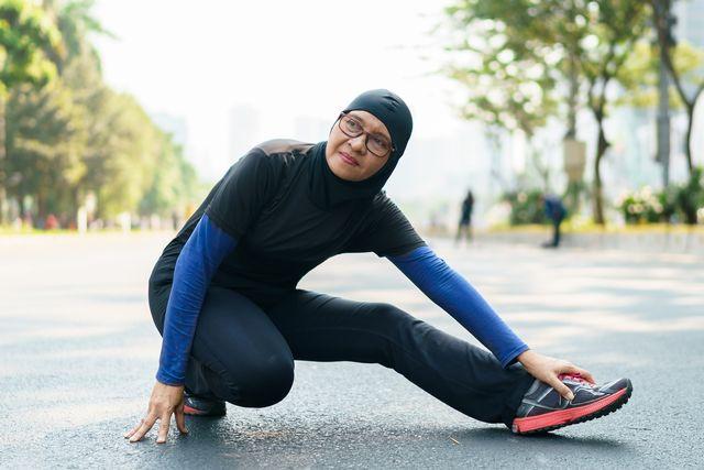 vrouw die hamstring stretch doet in buitenlucht