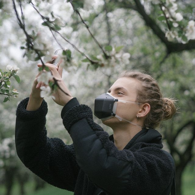 a person in a mask touching flowers on a tree