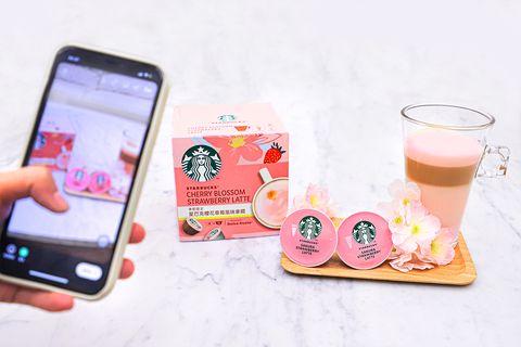 一個人拿手機拍粉色咖啡膠囊