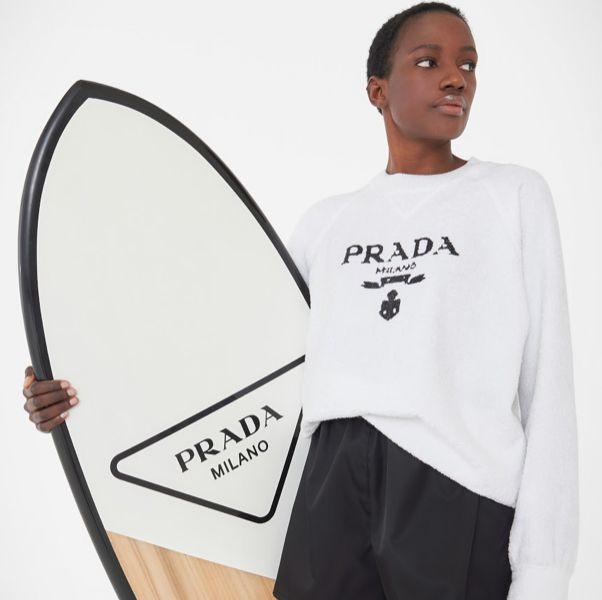一個人穿著白色衣服拿著白色衝浪板